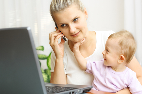 mom on phone and computer with baby